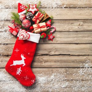 red stocking on wood background. Presents coming out of the top
